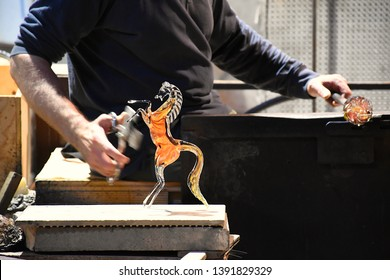 Murano, Venice, Italy – 19 April 2019: Glass blower forming a decorative glass horse at a traditional Murano glass manufactory