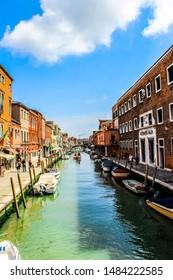 Murano / Venice / Italy - June 23, 2019: A view along Fondamenta Dei Vetrai and Fondamenta Daniele Manin footpaths in Murano. Boats rest along the side.