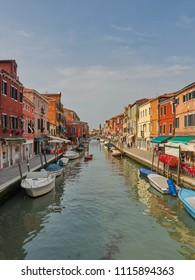 Murano, Venice/Italy - 6/6/2018: Canal in Murano with moored boats, flanked by colorful houses