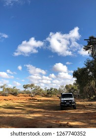 Murchison River, Western Australia / Australia - 22 July 2018: Rugged Landcruiser ute, 4WD vehicle on track next to Murchison River Homestead campground with gum trees and blue sky.