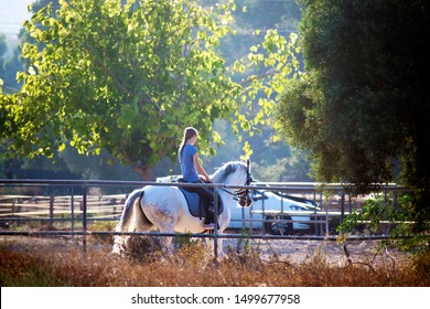 Murcia, Spain, August 28, 2019: Horse rider, riders at the sables. Sportswoman riding horse inside the stable. Women practicing sports. Women power.