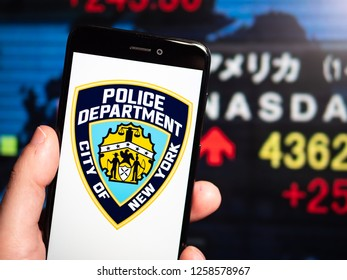 Murcia, Spain; Dic 14, 2018: New York City Police Department (NYPD) logo in phone with stock exchange screen on background. First person view