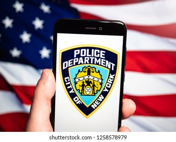 Murcia, Spain; Dic 14, 2018: New York City Police Department (NYPD) logo in phone with United States flag on background. NYPD is the primary law enforcement and investigation agency in New York
