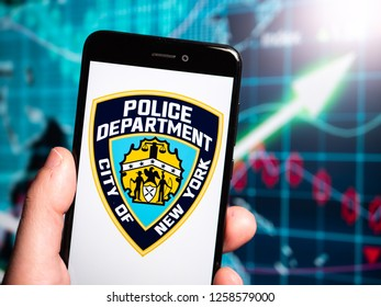 Murcia, Spain; Dic 14, 2018: New York City Police Department (NYPD) logo in phone with earnings graphic on background. NYPD is the primary law enforcement and investigation agency in New York