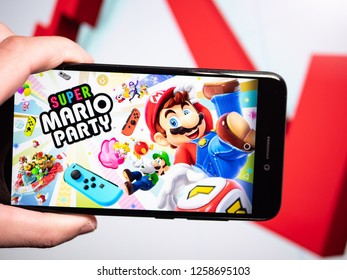 Murcia, Spain; Dic 14, 2018: Super Mario Party logo in phone with losses graphic on background. First person view