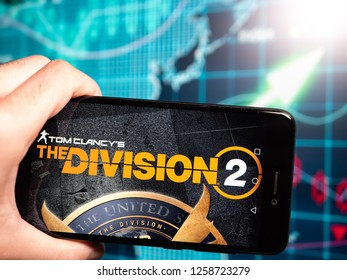 Murcia, Spain; Dic 14, 2018: Tom Clancy's The Division 2 logo in phone with earnings graphic on background. Tom Clancy's The Division 2 is an online action role-playing video game
