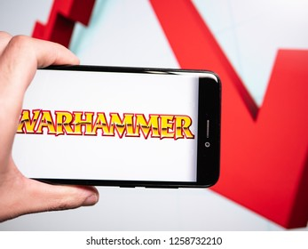 Murcia, Spain; Dic 14, 2018: Warhammer logo in phone with losses graphic on background. First person view