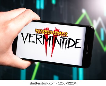 Murcia, Spain; Dic 14, 2018: Hand holding phone with Warhammer Vermintide II logo displayed in it with fluctuating graphic on background. First person view