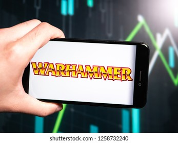 Murcia, Spain; Dic 14, 2018: Hand holding phone with Warhammer logo displayed in it with fluctuating graphic on background. First person view