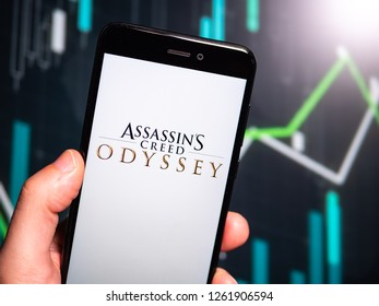 Murcia, Spain; Dic 17, 2018: Hand holding phone with Assassin's Creed Odyssey logo displayed in it  with fluctuating graphic on background. First person view