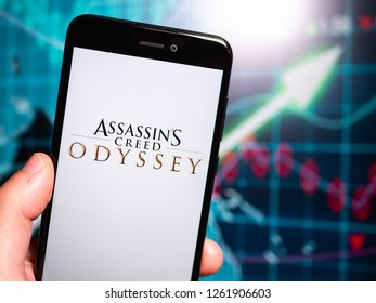 Murcia, Spain; Dic 17, 2018: Assassin's Creed Odyssey logo in phone with earnings graphic on background. Assassin's Creed Odyssey is a 2018 action role-playing video game