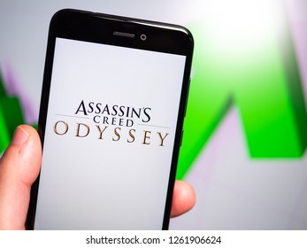 Murcia, Spain; Dic 17, 2018: Assassin's Creed Odyssey logo in phone with rises graphic on background. First person view