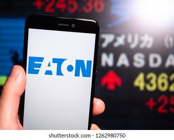 Murcia, Spain; Dic 17, 2018: Eaton Corporation logo in phone with New York stock exchange (NYSE) screen on background. First person view