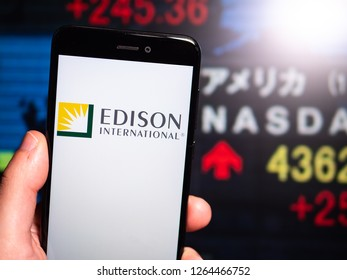 Murcia, Spain; Dic 17, 2018: Edison International logo in phone with New York stock exchange (NYSE) screen on background. First person view
