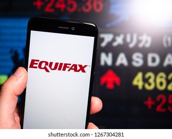 Murcia, Spain; Dic 17, 2018: Equifax logo in phone with New York stock exchange (NYSE) screen on background. First person view
