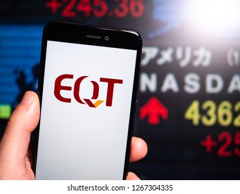 Murcia, Spain; Dic 17, 2018: EQT Corporation logo in phone with New York stock exchange (NYSE) screen on background. First person view