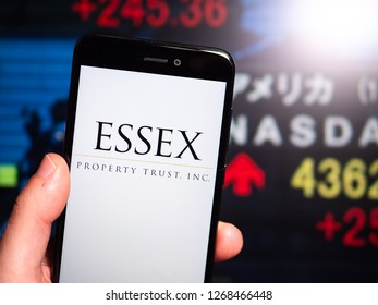 Murcia, Spain; Dic 17, 2018: Essex Property Trust logo in phone with New York stock exchange (NYSE) screen on background. First person view