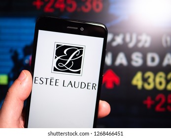 Murcia, Spain; Dic 17, 2018: Estee Lauder logo in phone with New York stock exchange (NYSE) screen on background. First person view