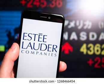 Murcia, Spain; Dic 17, 2018: Estee Lauder Companies logo in phone with New York stock exchange (NYSE) screen on background. First person view