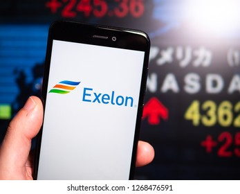 Murcia, Spain; Dic 17, 2018: Exelon Corporation logo in phone with New York stock exchange (NYSE) screen on background. First person view