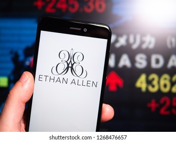 Murcia, Spain; Dic 17, 2018: Ethan Allen logo in phone with New York stock exchange (NYSE) screen on background. First person view
