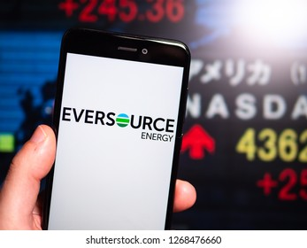 Murcia, Spain; Dic 17, 2018: Eversource Energy logo in phone with New York stock exchange (NYSE) screen on background. First person view