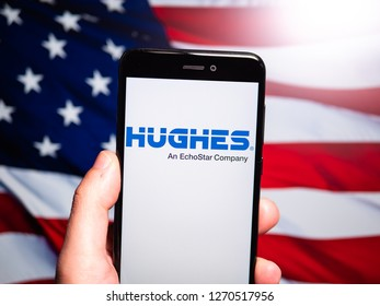 Murcia, Spain; Dic 17, 2018: Hughes Communications logo in phone with United States flag on background. Hughes Communications is a wholly owned subsidiary of EchoStar