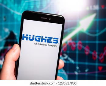 Murcia, Spain; Dic 17, 2018: Hughes Communications logo in phone with earnings graphic on background. Hughes Communications is a wholly owned subsidiary of EchoStar