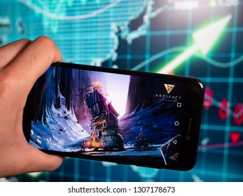 Murcia, Spain; Feb 7, 2019: Artifact logo in phone with earnings graphic on background. Artifact is a digital collectible card game