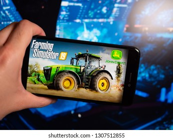 Murcia, Spain; Feb 7, 2019: Farming Simulator 19 icon in phone with esports tournament on background. Farming Simulator 19 is a modern farmer simulator video game
