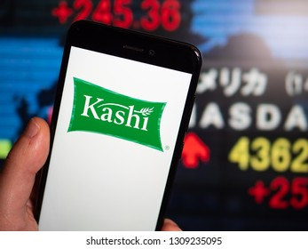Murcia, Spain; Feb 8, 2019: Kashi logo in phone with stock exchange screen on background. First person view