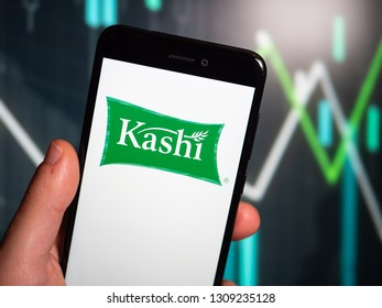 Murcia, Spain; Feb 8, 2019: Hand holding phone with Kashi logo displayed in it with fluctuating graphic on background. First person view