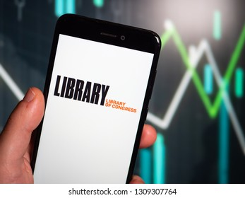 Murcia, Spain; Feb 8, 2019: Hand holding phone with Library of Congress (LOC) logo displayed in it with fluctuating graphic on background. First person view