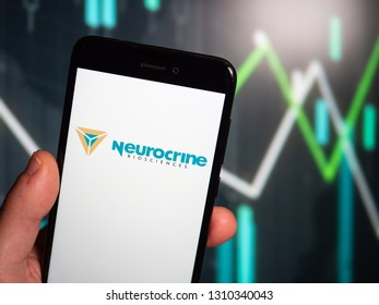 Murcia, Spain; Feb 8, 2019: Hand holding phone with Neurocrine Biosciences logo displayed in it with fluctuating graphic on background. First person view