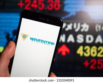 Murcia, Spain; Feb 8, 2019: Neurocrine Biosciences logo in phone with stock exchange screen on background. First person view