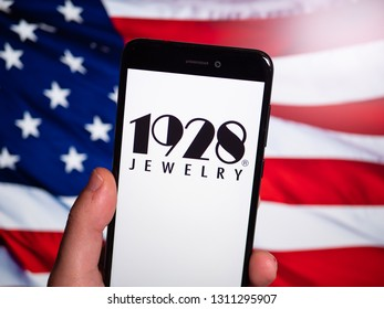 Murcia, Spain; Feb 8, 2019: 1928 Jewelry logo in phone with United States flag on background. 1928 Jewelry is a manufacturer and wholesaler of costume jewelry and novelties