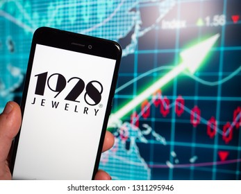 Murcia, Spain; Feb 8, 2019: 1928 Jewelry logo in phone with earnings graphic on background. 1928 Jewelry is a manufacturer and wholesaler of costume jewelry and novelties