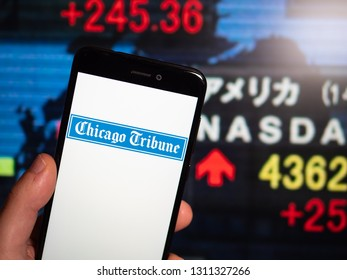 Murcia, Spain; Feb 8, 2019: Chicago Tribune logo in phone with stock exchange screen on background. First person view