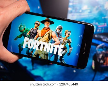 Murcia, Spain; Jan 16, 2019: Fortnite blue logo in phone with esports tournament on background. Fortnite is an online video game