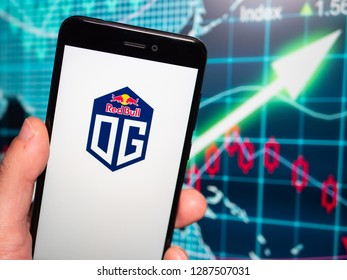 Murcia, Spain; Jan 16, 2019: Team OG logo in phone with earnings graphic on background. Team OG is a top ten esports team