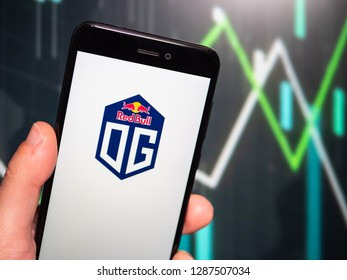 Murcia, Spain; Jan 16, 2019: Hand holding phone with Team OG logo displayed in it with fluctuating graphic on background. First person view