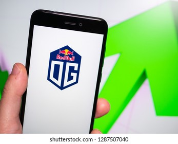 Murcia, Spain; Jan 16, 2019: Team OG logo in phone with rises graphic on background. First person view