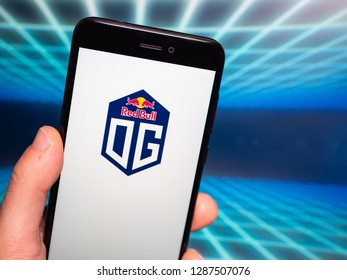 Murcia, Spain; Jan 16, 2019: Team OG logo in phone with computer screen on background. First person view