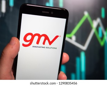 Murcia, Spain; Jan 17, 2019: Hand holding phone with GMV logo displayed in it with fluctuating graphic on background. First person view