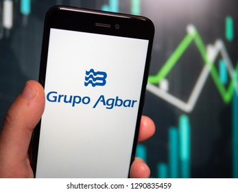 Murcia, Spain; Jan 17, 2019: Hand holding phone with Grupo Agbar logo displayed in it with fluctuating graphic on background. First person view