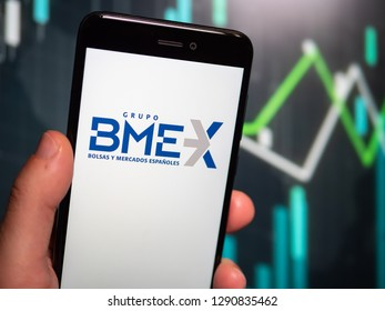 Murcia, Spain; Jan 17, 2019: Hand holding phone with Bolsas y Mercados Españoles (BME) logo displayed in it with fluctuating graphic on background. First person view