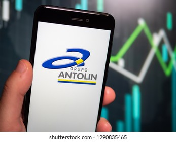 Murcia, Spain; Jan 17, 2019: Hand holding phone with Grupo Antolin logo displayed in it with fluctuating graphic on background. First person view