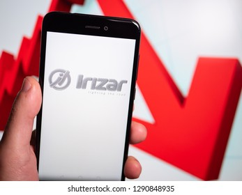 Murcia, Spain; Jan 17, 2019: Irizar logo in phone with losses graphic on background. First person view