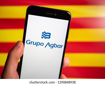 Murcia, Spain; Jan 17, 2019: Grupo Agbar logo in phone with Catalonia flag in background. Agbar is a Spanish company dedicated to services, distribution or treatment of water in Barcelona