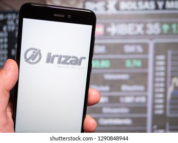 Murcia, Spain; Jan 17, 2019: Irizar logo in phone with stock exchange screen on background. First person view